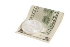 Pièce de monnaie argentée de bitcoin et cent billets de banque du dollar Images stock