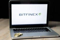 Pièce de monnaie de Bitcoin avec le logo d'échange de Bitfinex sur un écran d'ordinateur portable, Slovénie - 23 décembre 2018 images libres de droits