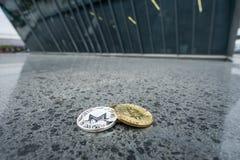 Pièce de monnaie de Bitcoin et de Monero, devant l'architecture d'affaires photographie stock