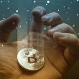 Pièce de monnaie de bitcoin de grippage de main d'homme d'affaires dans le courant léger photo modifiée la tonalité de double exp Photo libre de droits