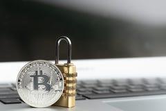 Pi?ce de monnaie de BitcoinBTC avec le cadenas se trouvant sur le fond d'ordinateur images stock