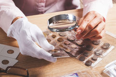 Pièce de monnaie collectable dans la main du ` s de femme par la loupe Images stock
