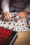 Pièce de monnaie collectable dans la main du ` s de femme par la loupe Images libres de droits