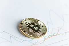Pièce de monnaie de cryptocurrency de bitcoin d'or sur graphe linéaire en hausse commerçant le ch Photographie stock