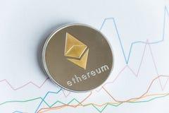 Pièce de monnaie de cryptocurrency d'ethereum d'or sur graphe linéaire en hausse commerçant c Photos stock