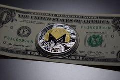 Pièce de monnaie de cryptocurrency de Monero sur un billet de banque du dollar photo stock