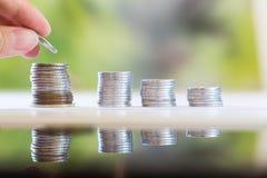 Pièce de monnaie d'économie de main avec le fond de jardin images stock