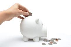 Pièce de monnaie d'économie de main de femme dans le ferroutage de blanc Photo stock
