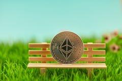 Pièce de monnaie d'éther sur le banc dans le jardin de la nature images stock