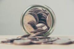 Pièce de monnaie d'argent dans la bouteille en verre Photo stock