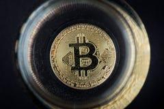 Pièce de monnaie d'or de Bitcoin Cryptocurrency en verre de l'eau image stock