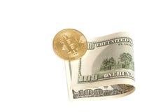 Pièce de monnaie d'or de bitcoin et cent billets de banque du dollar Photographie stock libre de droits