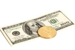 Pièce de monnaie d'or de bitcoin et cent billets de banque du dollar d'isolement dessus Images stock