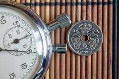 Pièce de monnaie danoise avec une dénomination d'un couronne et chronomètre sur la table en bois - arrière photo stock