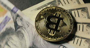 Pièce de monnaie de Bitcoin sur les billets de banque du dollar tournant sur un fond noir clips vidéos