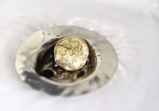 Pièce de monnaie de livre BRITANNIQUE dans le drain d'évier argenté Photos libres de droits