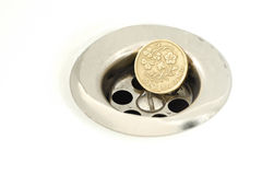 Pièce de monnaie de livre BRITANNIQUE dans le drain d'évier argenté Images stock