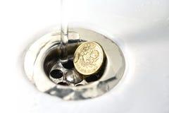 Pièce de monnaie de livre BRITANNIQUE dans le drain d'évier argenté Photographie stock