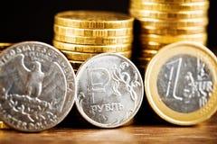 Pièce de monnaie de rouble russe entre le dollar et l'euro Image stock