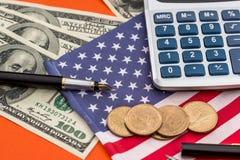 Pièce de monnaie des Etats-Unis avec des billets de banque du dollar sur le drapeau Images stock