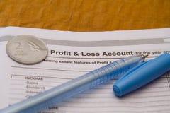Pièce de monnaie et stylo de roupie d'Indin sur le compte de profits et pertes photo stock