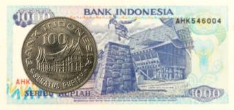 pièce de monnaie de la roupie 100 indonésienne contre la note de la roupie 1000 indonésienne photo stock