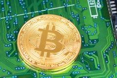 Pièce de monnaie métallique de Bitcoin sur le conseil électronique vert Photo stock