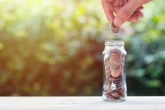 Pièce de monnaie de participation de main au-dessus des pièces de monnaie dans le pot en verre sur la table en bois photo libre de droits