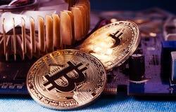 Pièce de monnaie physique de Bitcoin d'or sur une carte vidéo d'ordinateur Nouveau cryptocurrency mondial indépendant Photos libres de droits