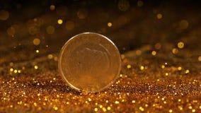 Pièce de monnaie de 1 roulement d'euro sur la poudre d'or sur le fond noir, banque de vidéos