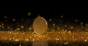 Pièce de monnaie de 1 roulement d'euro sur la poudre d'or sur le fond noir, mouvement lent clips vidéos