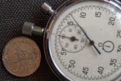 Pièce de monnaie thaïlandaise avec une dénomination du baht 5 (arrière) et du chronomètre sur le contexte brun de denim - fond d' Photographie stock libre de droits