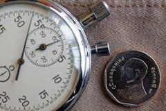 Pièce de monnaie thaïlandaise avec une dénomination du baht cinq (arrière) et du chronomètre sur le contexte beige usé de jeans - Photographie stock libre de droits