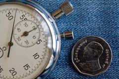 Pièce de monnaie thaïlandaise avec une dénomination du baht cinq (arrière) et du chronomètre sur le contexte bleu de denim - fond Photo libre de droits