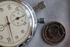 Pièce de monnaie thaïlandaise avec une dénomination du baht cinq (arrière) et du chronomètre sur le contexte gris de denim - fond Images libres de droits