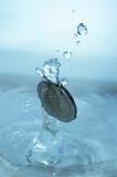 Pièce de monnaie tombant dans l'eau Image stock