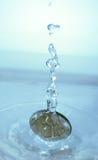 Pièce de monnaie tombant dans l'eau Photo libre de droits
