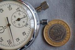 Pièce de monnaie turque avec une dénomination d'une Lire (arrière) et de chronomètre sur le contexte gris de denim - fond d'affai Photographie stock