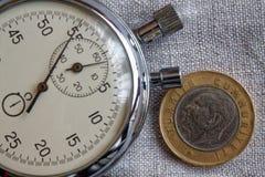 Pièce de monnaie turque avec une dénomination d'une Lire (arrière) et de chronomètre sur le contexte gris de lin - fond d'affaire Photo libre de droits