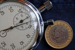Pièce de monnaie turque avec une dénomination d'une Lire (arrière) et de chronomètre sur le contexte porté foncé de blues-jean -  Photographie stock libre de droits