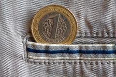 Pièce de monnaie turque avec une dénomination d'une Lire dans la poche de jeans beiges de denim avec la rayure bleue Photo stock