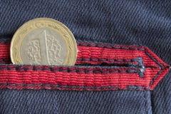 Pièce de monnaie turque avec une dénomination d'une Lire dans la poche de jeans bleus usés de denim avec la rayure rouge Photo libre de droits