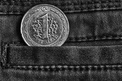 Pièce de monnaie turque avec une dénomination d'une Lire dans la poche de jeans foncés de denim, tir monochrome Images libres de droits