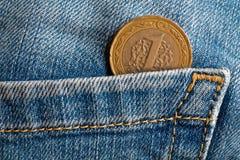Pièce de monnaie turque avec une dénomination d'une Lire dans la poche de vieux jeans utilisés bleus de denim Image stock