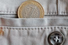 Pièce de monnaie turque avec une dénomination de 1 Lire dans la poche de jeans beiges de denim avec le bouton Image libre de droits