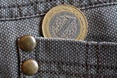 Pièce de monnaie turque avec une dénomination de 1 Lire dans la poche de jeans bruns de denim Images libres de droits