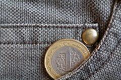 Pièce de monnaie turque avec une dénomination de 1 Lire dans la poche de jeans bruns usés de denim Photos stock