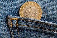 Pièce de monnaie turque avec une dénomination de 1 Lire dans la poche de jeans utilisés bleus de denim Photo stock