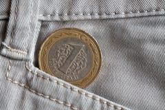Pièce de monnaie turque avec une dénomination de 1 Lire dans la poche de vieux jeans beiges de denim Photographie stock libre de droits