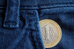 Pièce de monnaie turque avec une dénomination de 1 Lire dans la poche de vieux jeans bleus de denim Photos libres de droits